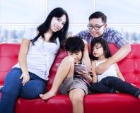 Famiglia felice che si rilassa sul sofà rosso all'appartamento fotografia stock