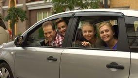 Famiglia felice che si siede in automobile e che sorride nella macchina fotografica, servizio di acquisto dell'automobile stock footage