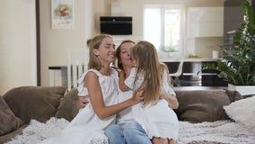 Famiglia felice che si siede insieme sullo strato nel salone La madre e le sue due figlie si divertono la seduta sul sofà archivi video