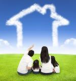 Famiglia felice che si siede su un prato con la casa delle nuvole Fotografie Stock Libere da Diritti