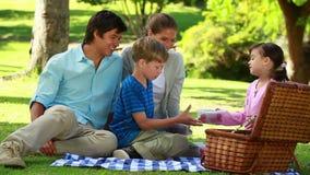 Famiglia felice che si siede su una coperta durante il picnic stock footage