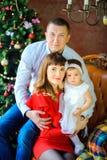 Famiglia felice che si siede su una sedia vicino ad un albero di Natale festivo fotografia stock