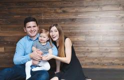 Famiglia felice che si siede sul pavimento con il loro piccolo bambino Fotografia Stock Libera da Diritti