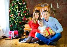 Famiglia felice che si siede sul pavimento con un regalo nelle mani e nel sorridere fotografia stock libera da diritti
