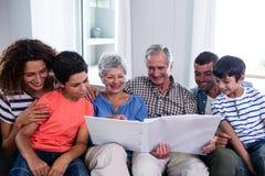 Famiglia felice che si siede sul sofà e che esamina album di foto Immagine Stock