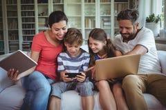 Famiglia felice che si siede sul sofà e che per mezzo del computer portatile, del telefono cellulare e della compressa digitale immagini stock libere da diritti