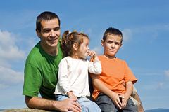 Famiglia felice che si siede sulla pietra Immagine Stock