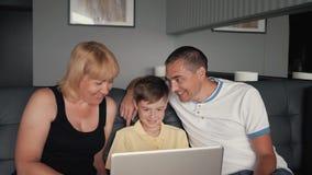 Famiglia felice che si siede sullo strato che chiacchiera con i parenti su Internet Tecnologia moderna nel servizio della gente stock footage