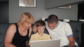 Famiglia felice che si siede sullo strato che chiacchiera con i parenti su Internet Tecnologia moderna nel servizio della gente video d archivio