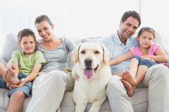 Famiglia felice che si siede sullo strato con il loro animale domestico labrador fotografia stock