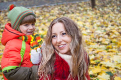 Famiglia felice che sorride e che tiene le foglie di autunno immagini stock