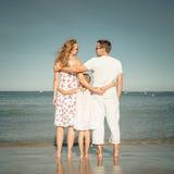 Famiglia felice che sta alla spiaggia Immagini Stock Libere da Diritti