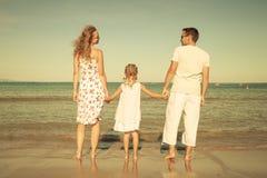 Famiglia felice che sta alla spiaggia Fotografia Stock