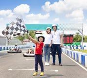 Famiglia felice che sta in movimento la pista di corsa del kart fotografia stock libera da diritti