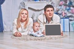 Famiglia felice che tiene una cartolina di Natale in bianco, trovantesi sul tappeto in un salone accogliente immagine stock libera da diritti