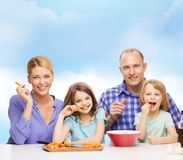 Famiglia felice con due bambini che mangiano a casa Fotografia Stock Libera da Diritti