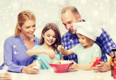 Famiglia felice con due bambini che producono insalata a casa Fotografie Stock Libere da Diritti