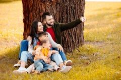 Famiglia felice con due bambini che si siedono insieme sull'erba in parco e che prendono un selfie immagini stock