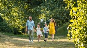 Famiglia felice con due bambini che si tengono per mano durante la passeggiata ricreativa fotografie stock libere da diritti