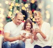 Famiglia felice con gli smartphones Immagine Stock Libera da Diritti