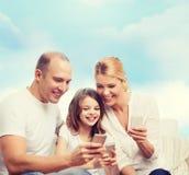 Famiglia felice con gli smartphones Fotografia Stock