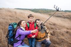 Famiglia felice con gli zainhi che prendono selfie Fotografia Stock