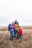 Famiglia felice con gli zainhi che stanno nell'erba Fotografia Stock