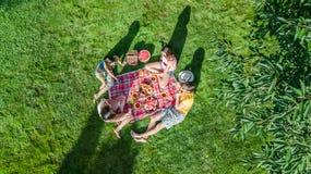 Famiglia felice con i bambini che hanno picnic in parco, genitori con i bambini che si siedono sull'erba del giardino e che mangi fotografie stock libere da diritti