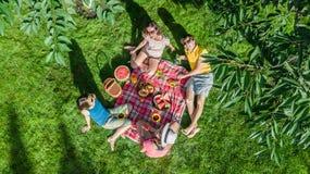 Famiglia felice con i bambini che hanno picnic in parco, genitori con i bambini che si siedono sull'erba del giardino e che mangi fotografia stock