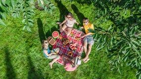 Famiglia felice con i bambini che hanno picnic in parco, genitori con i bambini che si siedono sull'erba del giardino e che mangi immagine stock