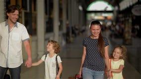 Famiglia felice con i bambini che vanno sulla stazione ferroviaria, sui genitori e sui bambini viaggianti e camminanti sull'aerop video d archivio