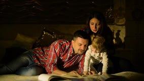 Famiglia felice con i libri di bambini della lettura della figlia del bambino a letto alla notte stock footage