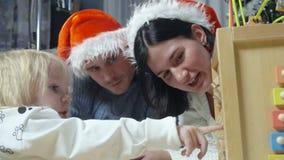Famiglia felice con il bambino in cappelli del ` s di Santa video d archivio