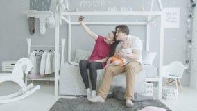 Famiglia felice con il bambino che prende selfie unito a casa stock footage