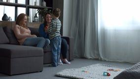 Famiglia felice con il bambino che si rilassa nella stanza domestica archivi video