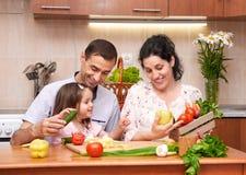 Famiglia felice con il bambino nell'interno domestico della cucina con la frutta e le verdure fresche, donna incinta, concetto sa fotografia stock libera da diritti