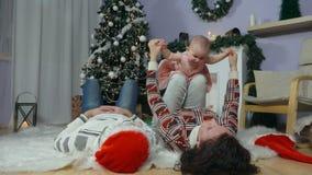 Famiglia felice con il bambino sotto l'albero di Natale archivi video