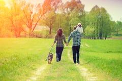 Famiglia felice con il cane che cammina sulla strada non asfaltata rurale fotografia stock libera da diritti