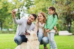Famiglia felice con il cane che prende selfie dallo smartphone fotografia stock libera da diritti