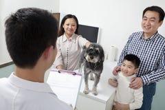Famiglia felice con il cane di animale domestico nell'ufficio del veterinario immagine stock