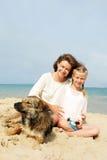 Famiglia felice con il cane sulla spiaggia Immagini Stock Libere da Diritti