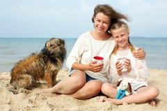 Famiglia felice con il cane sulla spiaggia Immagini Stock