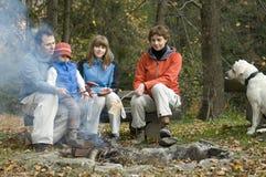 Famiglia felice con il cane vicino a fuoco di accampamento Fotografia Stock Libera da Diritti