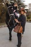 Famiglia felice con il cavallo nero Immagini Stock