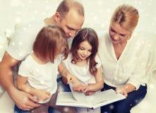 Famiglia felice con il libro a casa Immagini Stock
