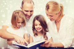 Famiglia felice con il libro a casa Fotografie Stock Libere da Diritti