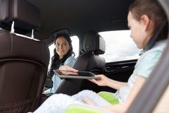 Famiglia felice con il pc della compressa che guida in automobile Fotografie Stock Libere da Diritti