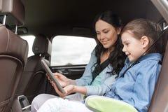 Famiglia felice con il pc della compressa che guida in automobile Fotografia Stock Libera da Diritti