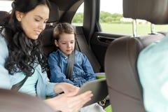 Famiglia felice con il pc della compressa che guida in automobile Fotografia Stock