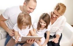 Famiglia felice con il pc della compressa e la carta di credito Fotografia Stock Libera da Diritti